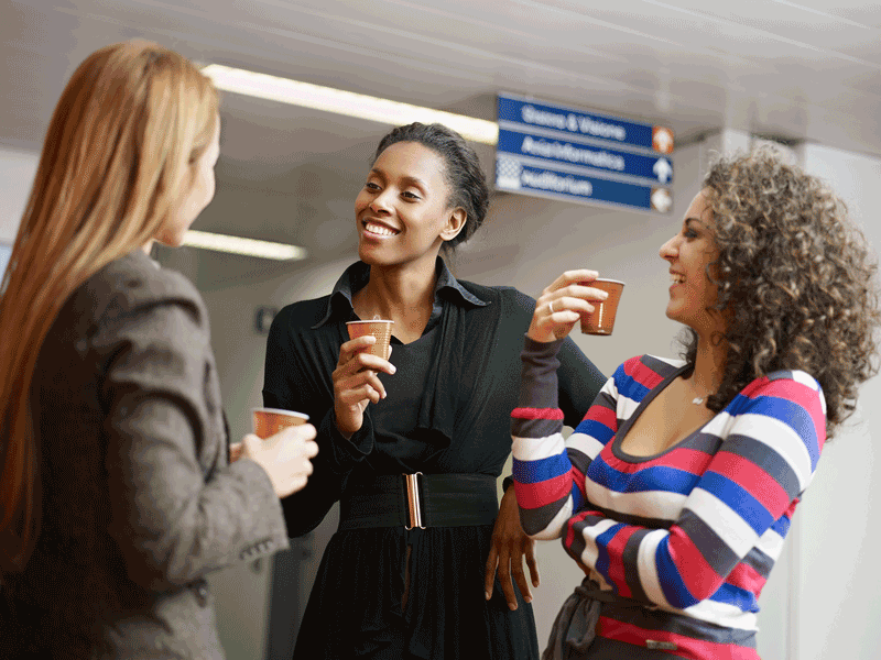 Women connecting over conversation share a sense of belonging that helps wellbeing at the office.
